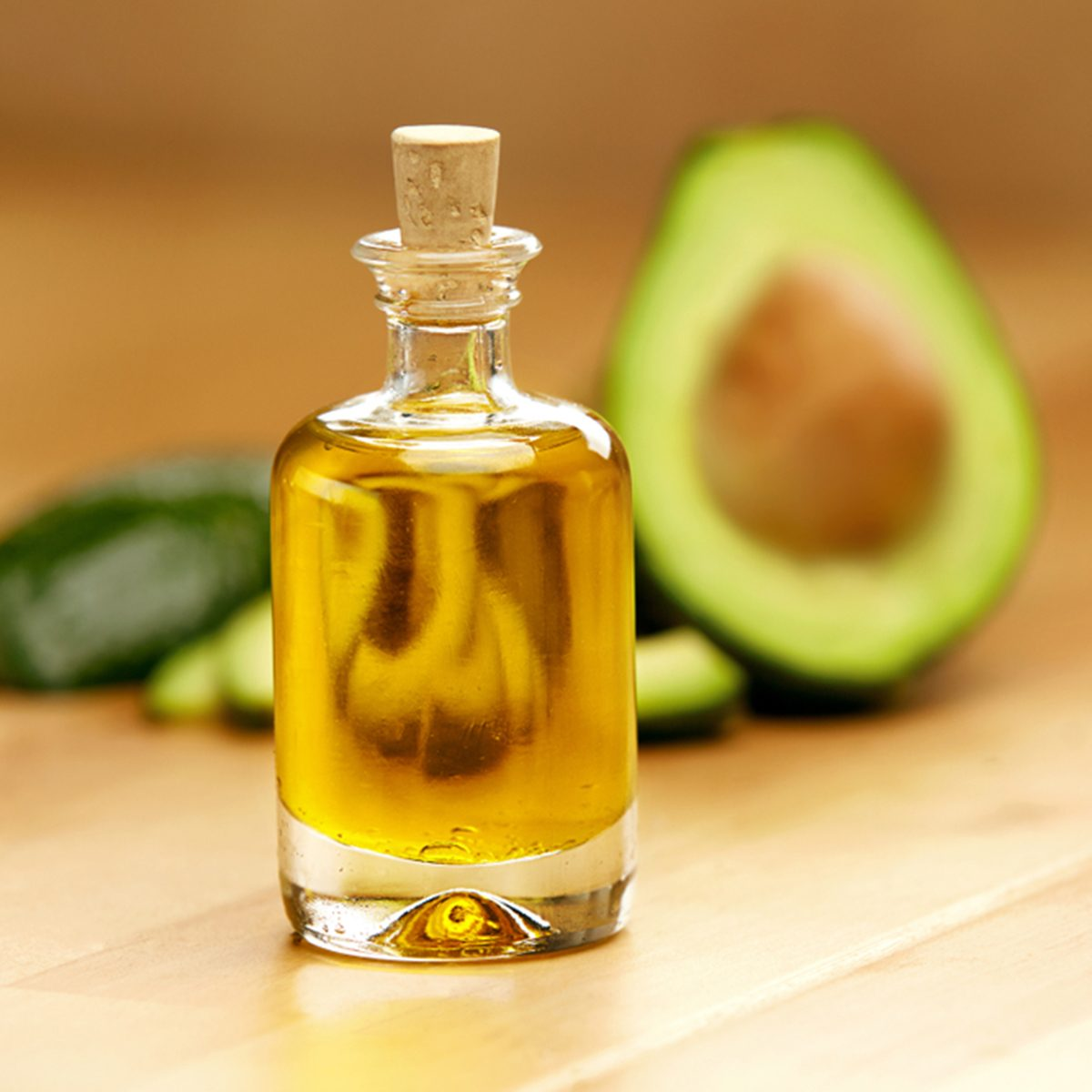 Food Ingredients. Avocado Oil In Bottle With Avocado On Table