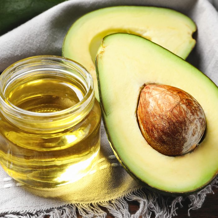 Jar with oil and ripe fresh avocado on table