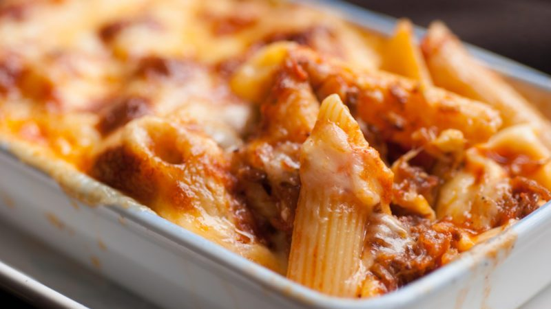 Baked penne pasta with tomato sauce and cheese in White bowl