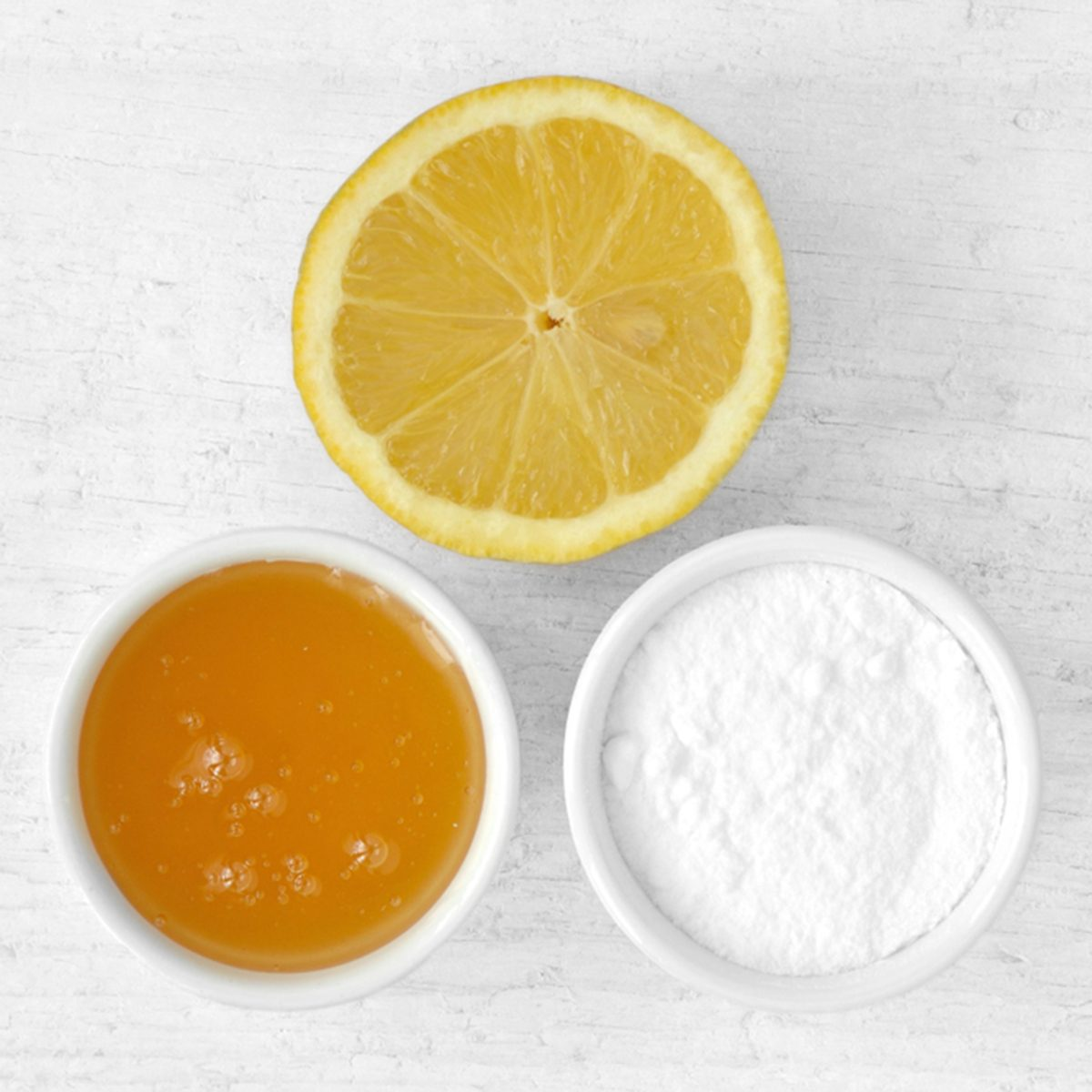 Homemade face mask made out of lemon juice, honey and baking soda on wooden background