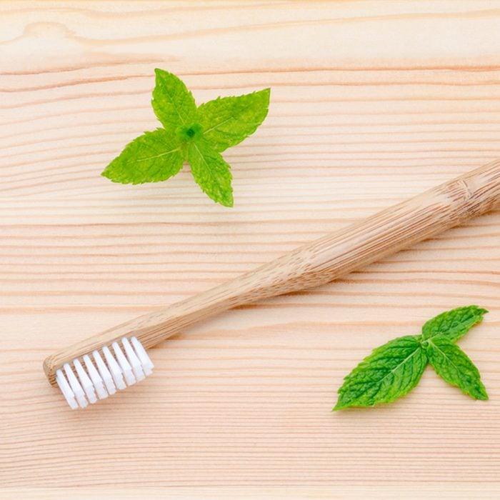 alternative wood toothbrush and xylitol, soda, powder, salt, mint on wooden