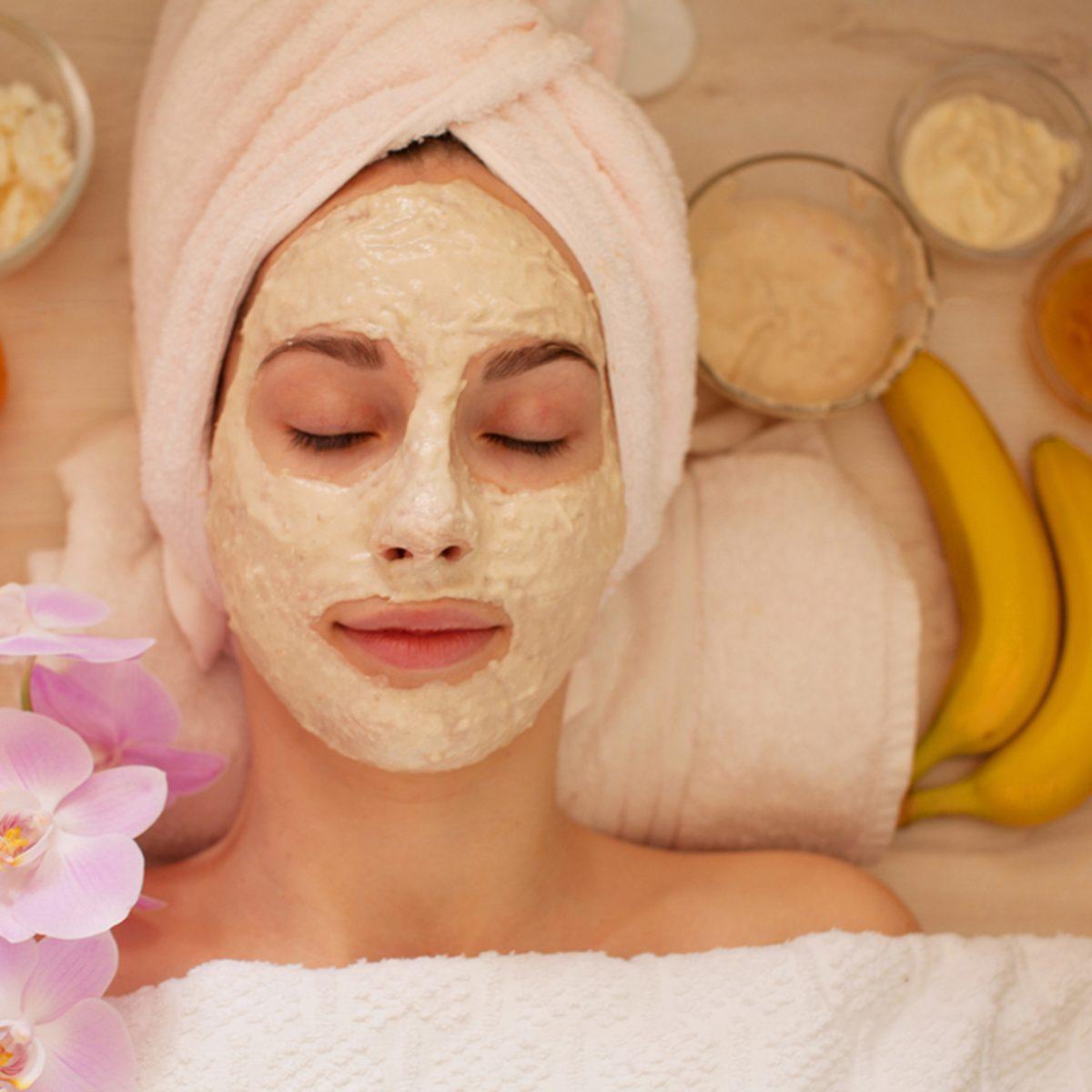 Spa Woman applying Facial clay Mask.