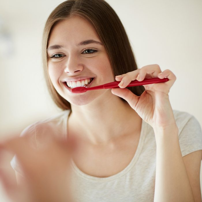 Young woman brushing her teeth at mirror