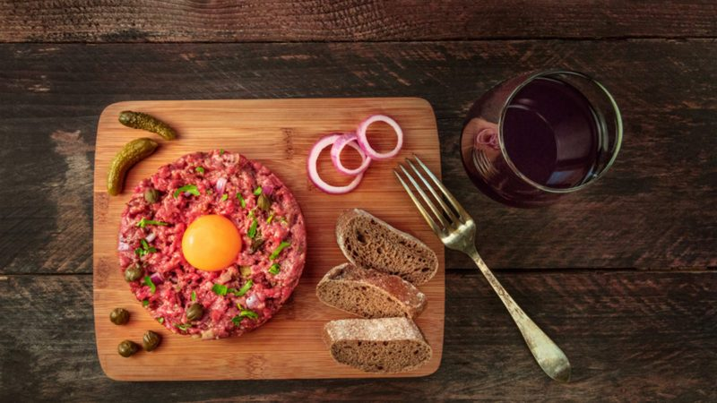 A photo of a steak tartare with a raw egg yolk, gherkins, capers, rye bread, purple onions, a glass of red wine, and a fork, shot from above on a dark rustic texture