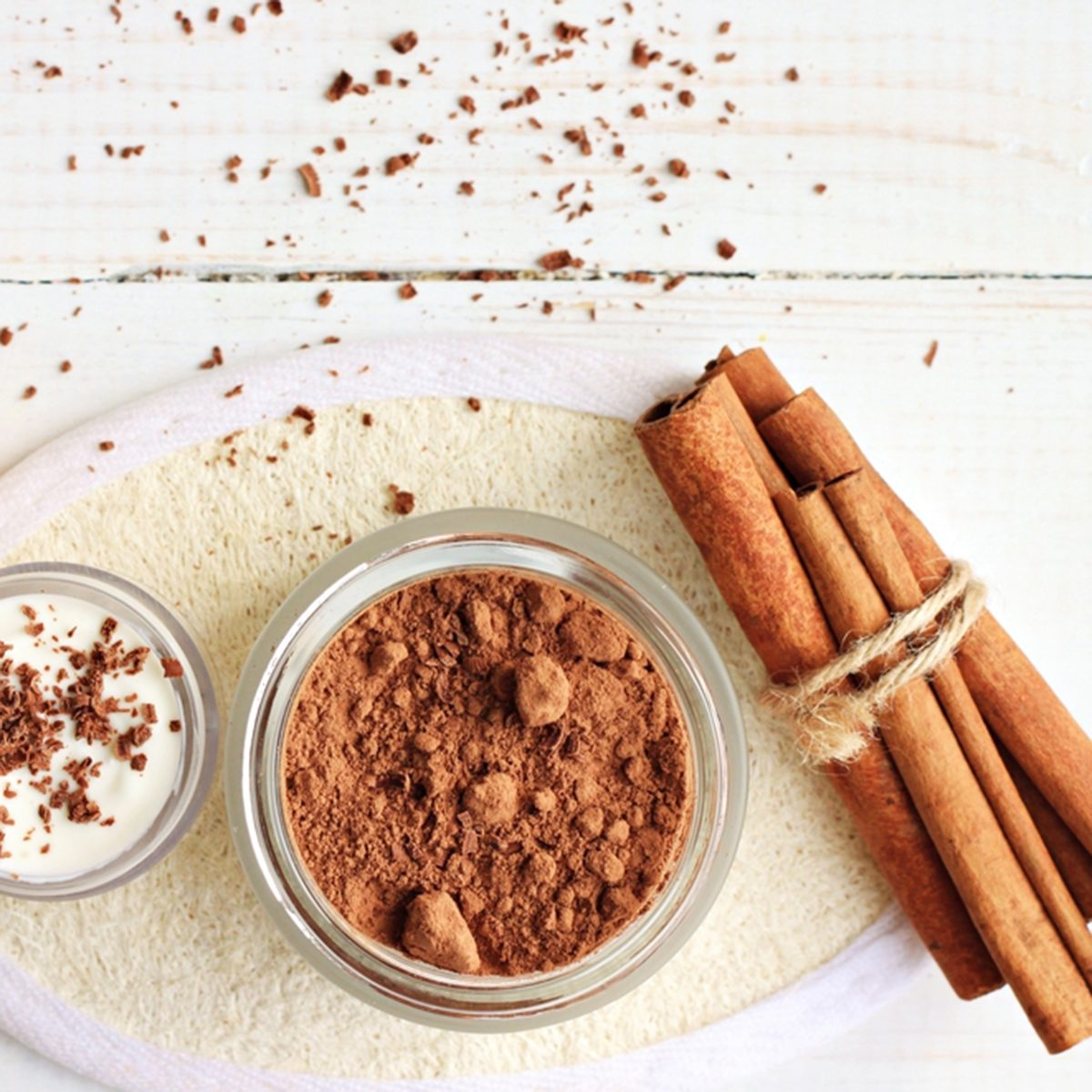 Chocolate skin treatment. Cosmetic jar with cocoa, cinnamon sticks, chocolate body butter.