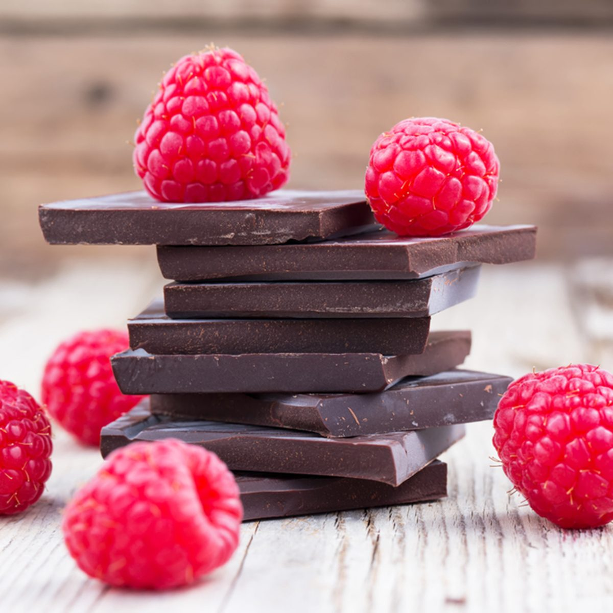 Dark chocolate stack with fresh raspberries, on wooden table.