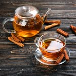 Cup and teapot with aromatic hot cinnamon tea on wooden table