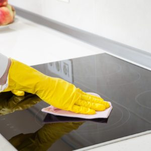 woman showing how to clean a glass stovetop