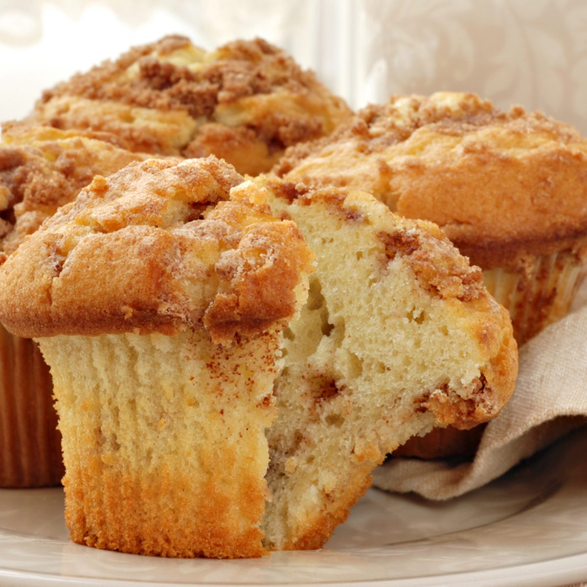 Freshly baked cinnamon muffins with sunlit window in background.