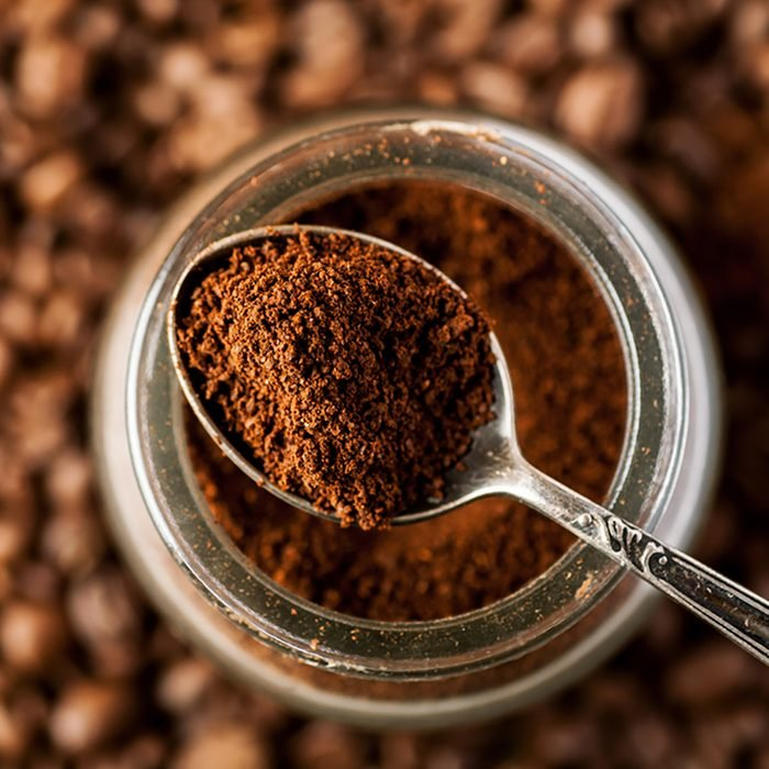 Ground coffee in a metal spoon on a top of glass jar, shallow depth of field