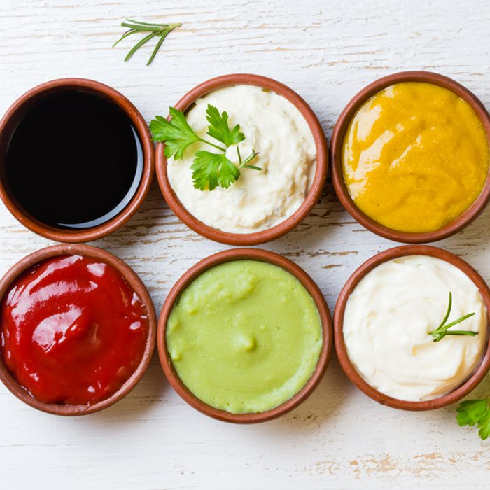 Sauces ketchup, mustard, mayonnaise, wasabi, soy sauce in clay bowls on wooden white background