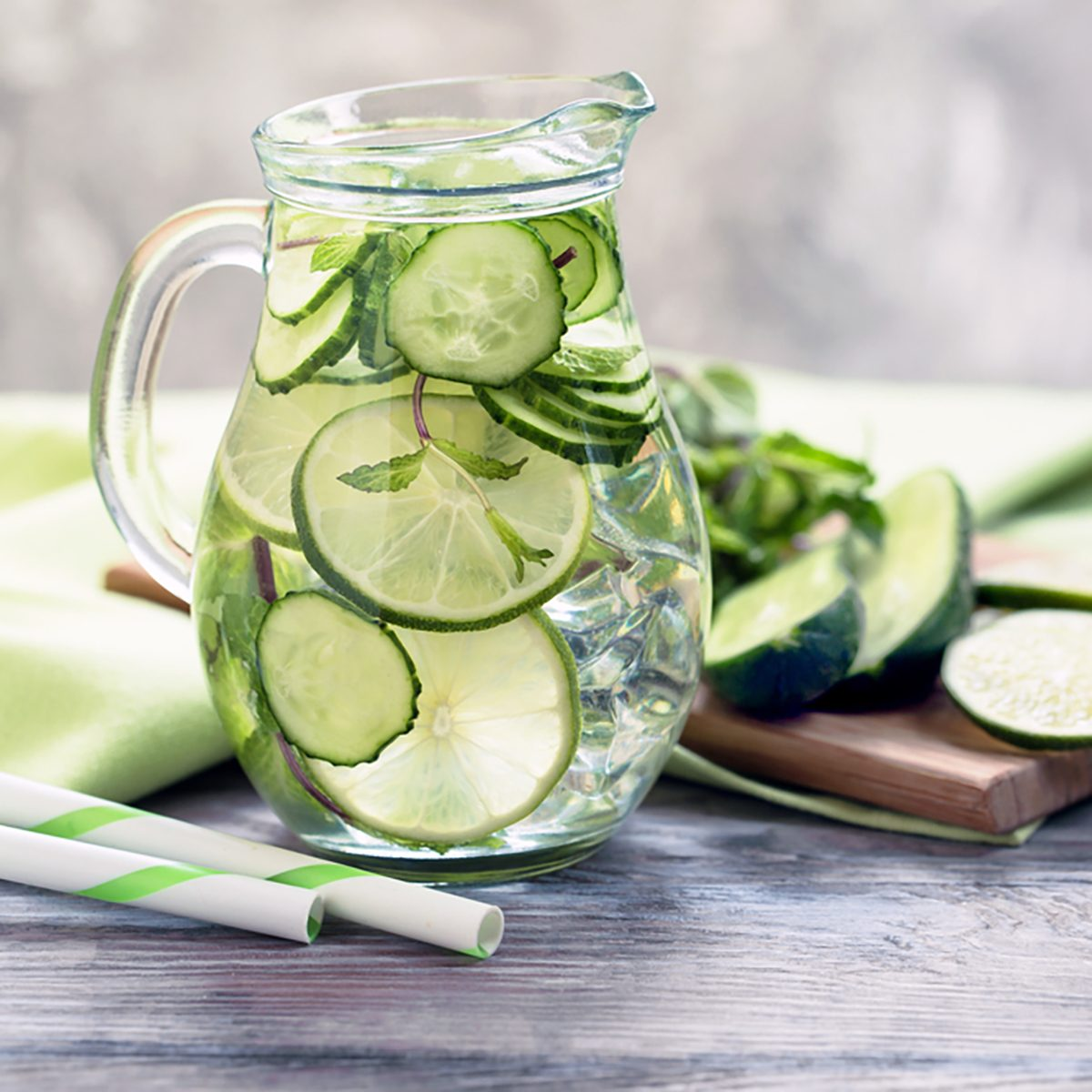 Infused water with cucumber, lime and mint on grey rustic background