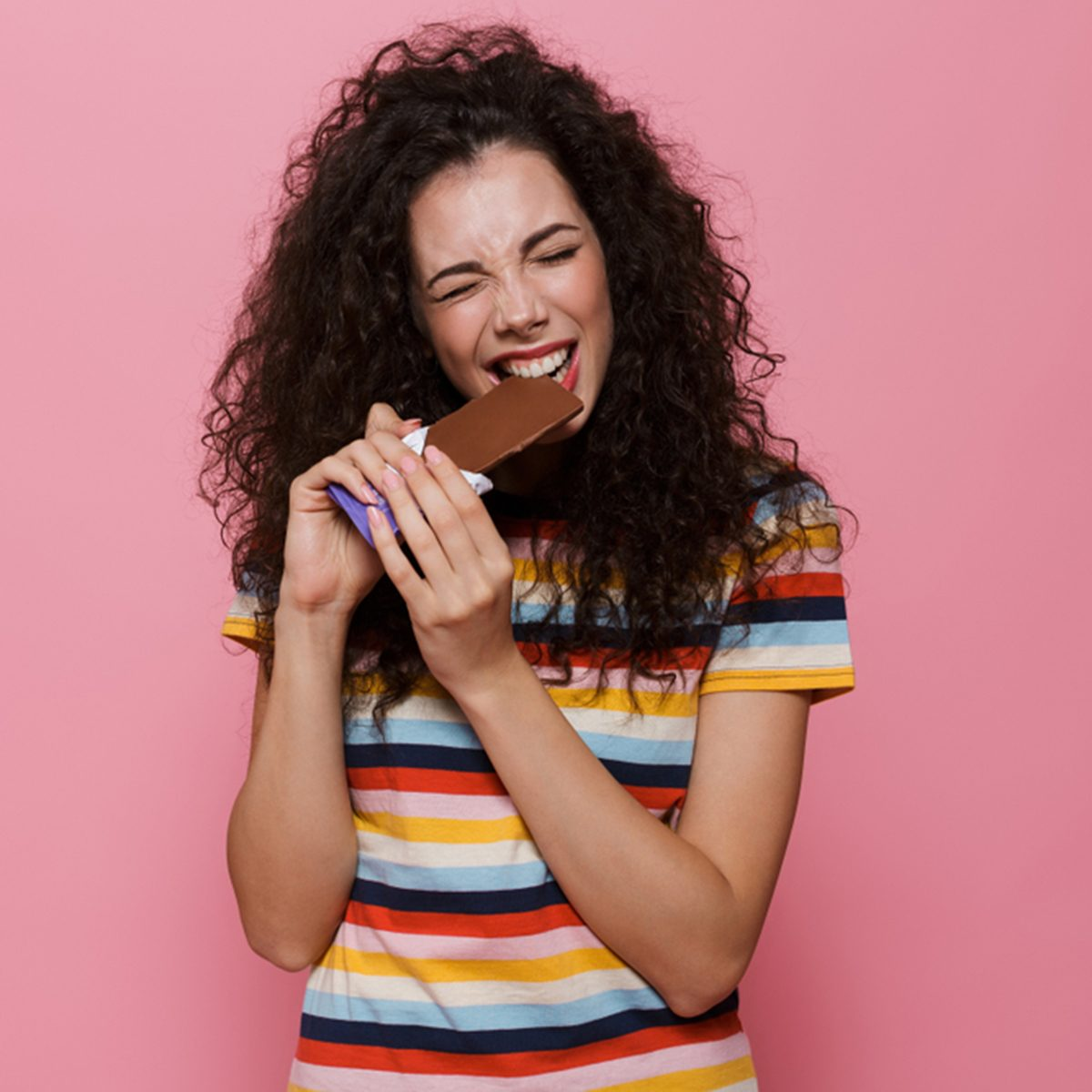 Photo of brunette woman 20s with curly hair eating chocolate bar isolated over pink background