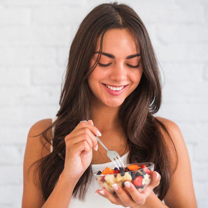 Closeup Of Smiling Young Woman Eating Granola Fruit Parfait.