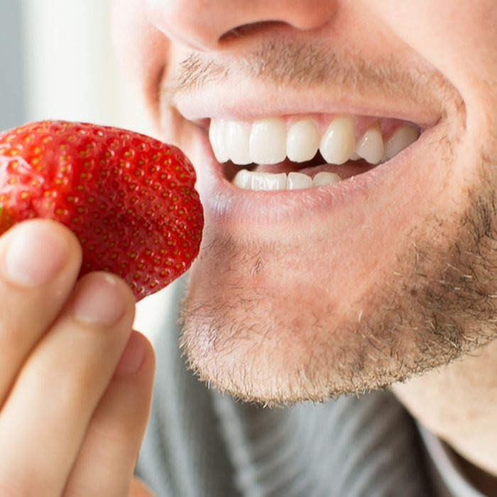 Young man holding a strawberry and smiling