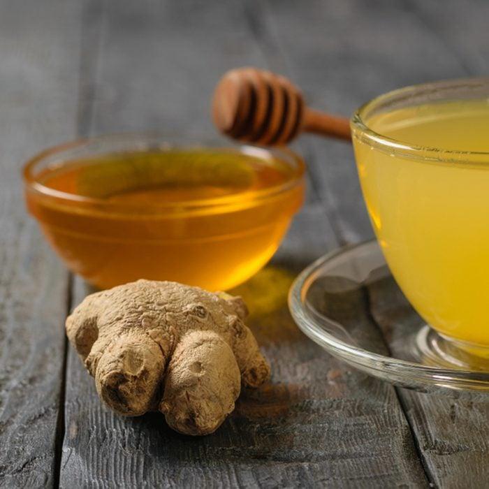 Drink ginger root, lemon, orange, honey and cinnamon on a black wooden table.