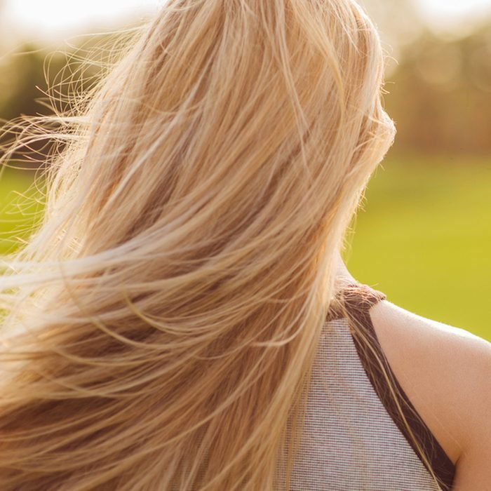 Beautiful young woman with long blonde hair in motion turned back, at sunset time on the green golf field.