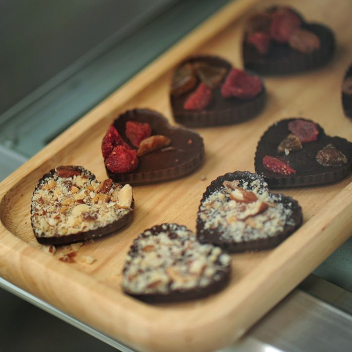 Heart-shaped chocolate sprinkled with crushed almonds and dried strawberries.