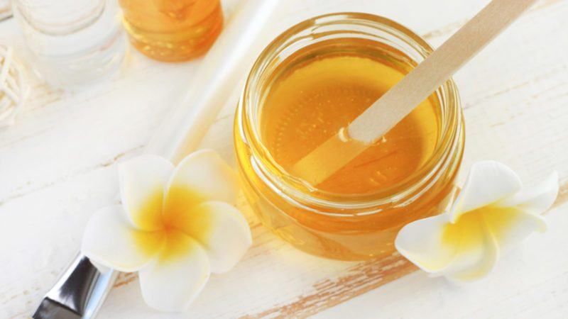 Glass jar of golden honey closep with frangipani flowers.