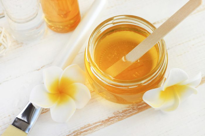 Glass jar of golden honey closep with frangipani flowers.