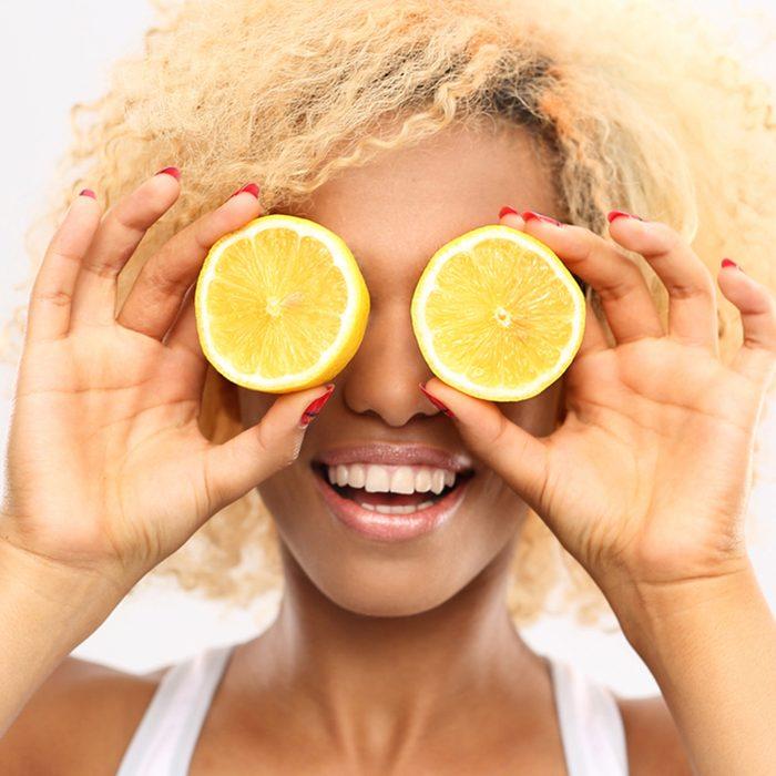 Dark skinned girl with fruits lemon