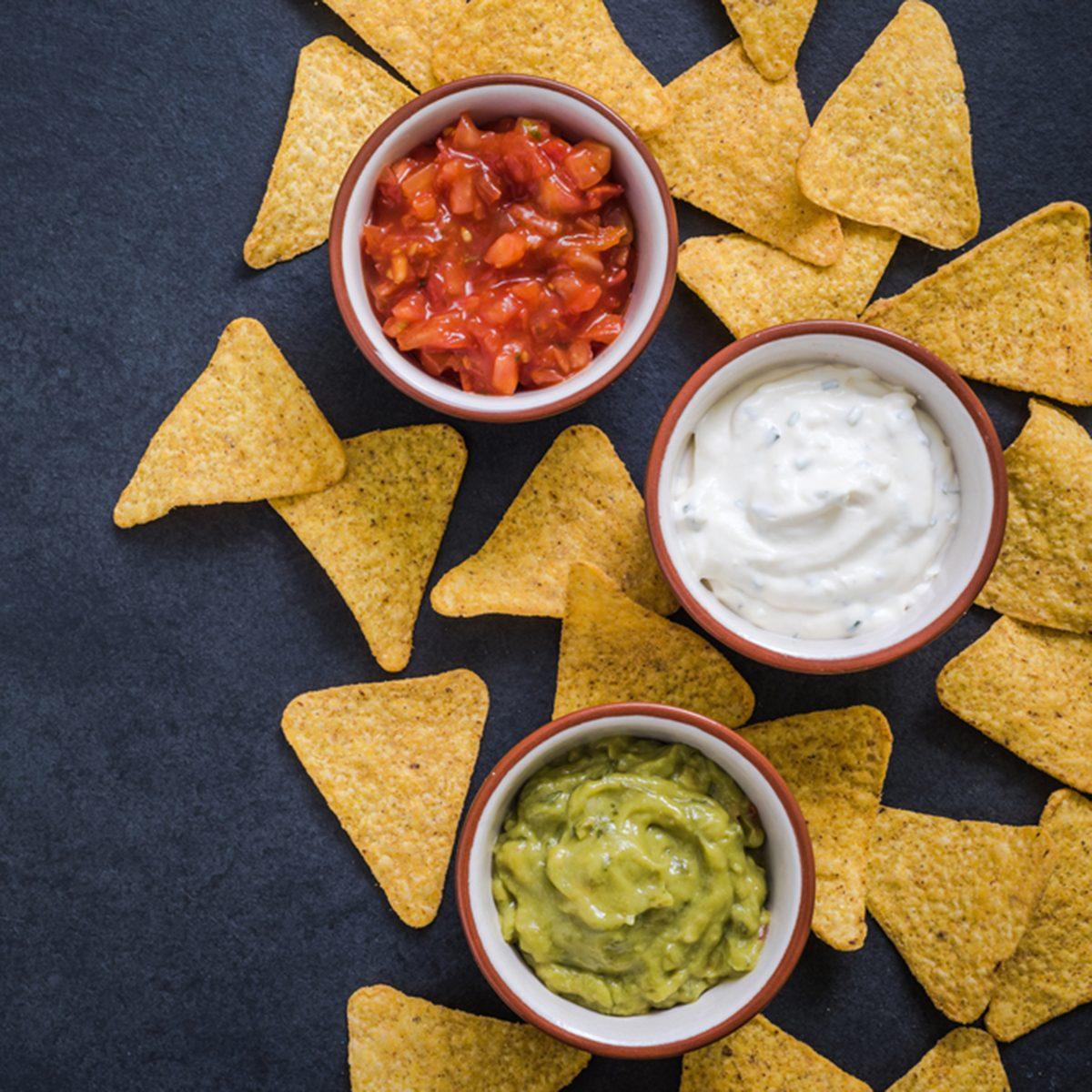 nachos with dips border background on dark slate