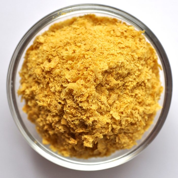Nutritional yeast in a bowl close-up on white background