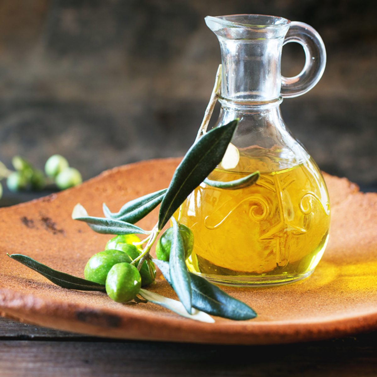 Bottle of olive oil with olive branch in handmade clay plate over wooden table.
