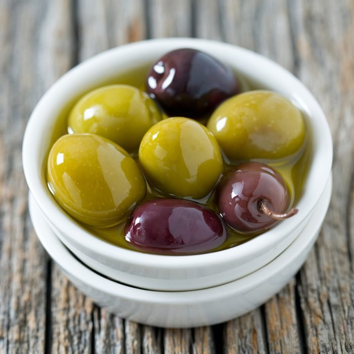 olives in a bowl on wooden surface