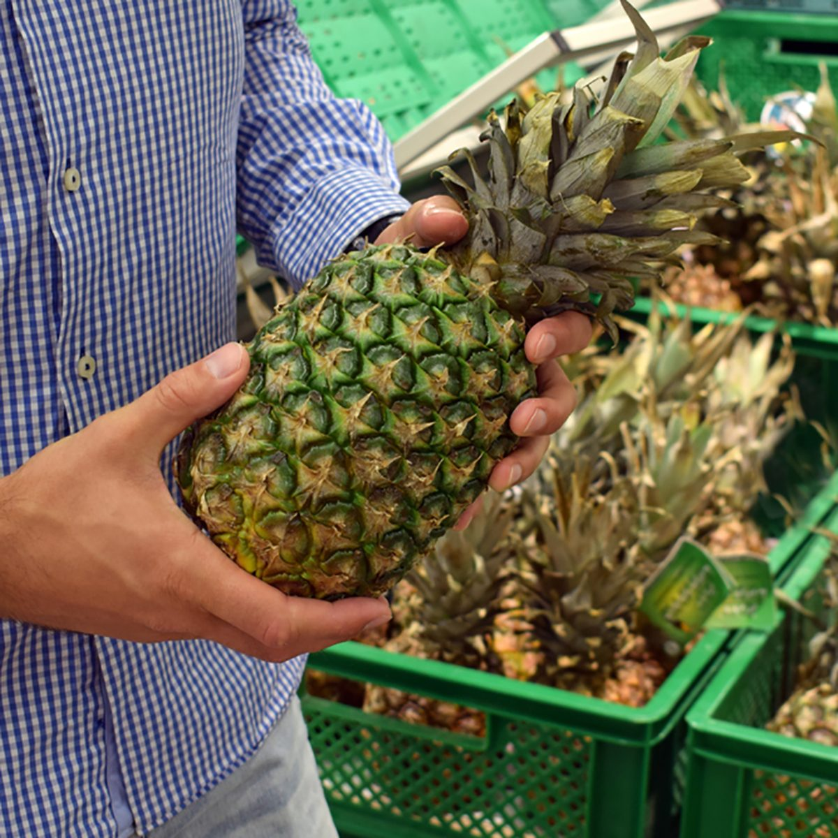 The guy chooses pineapples in the supermarket.