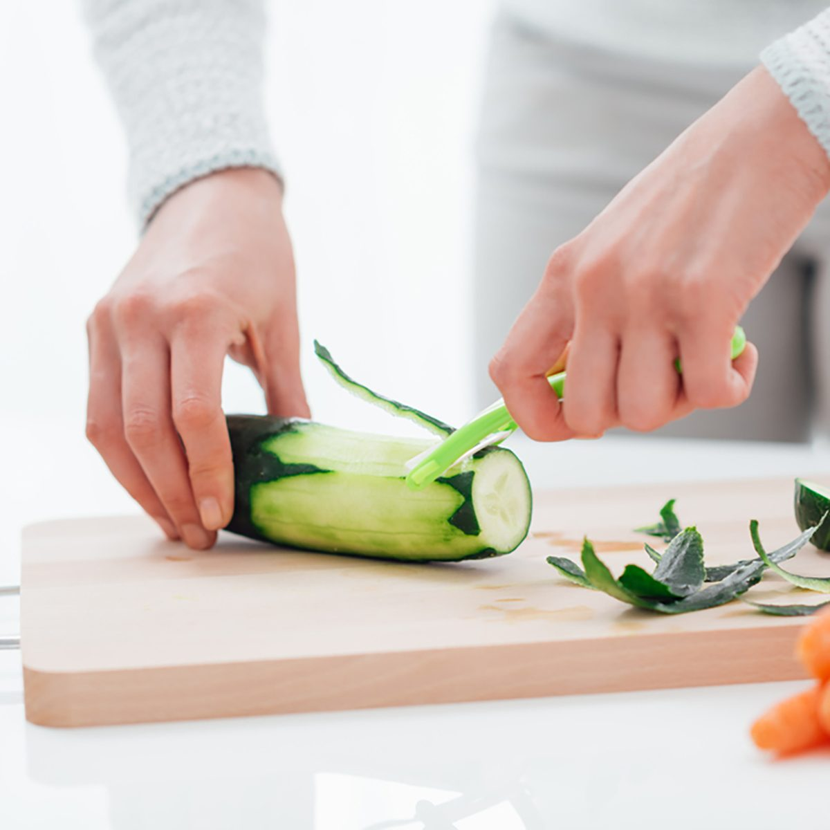 Woman cooking healthy food in her kitchen, she is peeling a fresh cucumber on the chopping board
