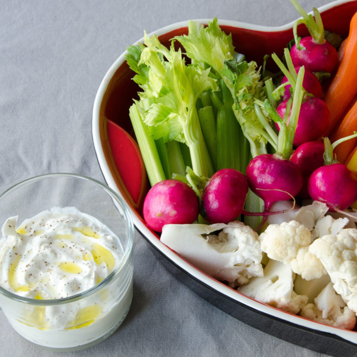 Vegetables in a heart-shaped tray ready to eat on light background.