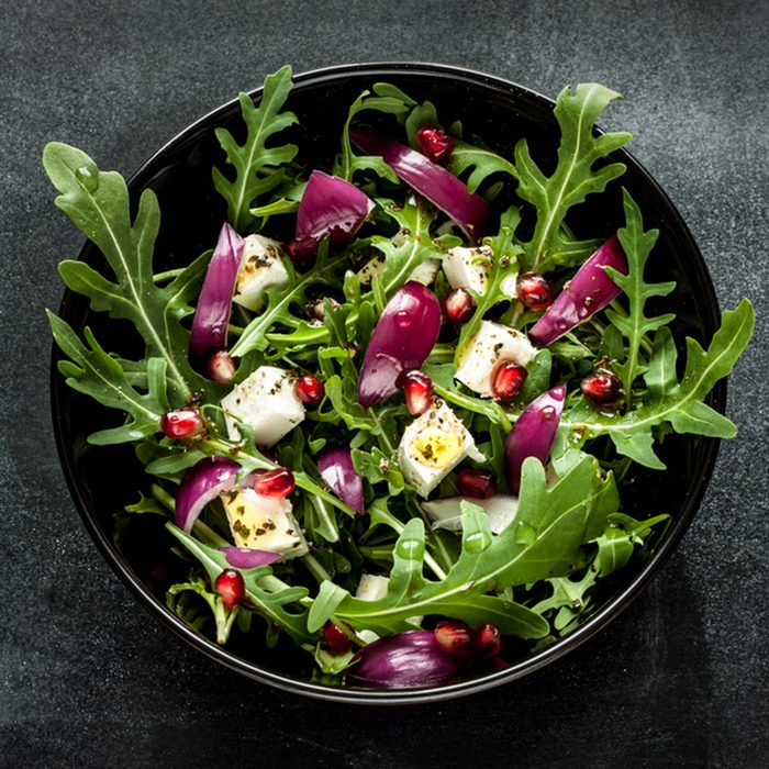 Fresh spring salad with rucola, feta cheese, red onion and pomegranate seeds in black bowl on chalkboard background.