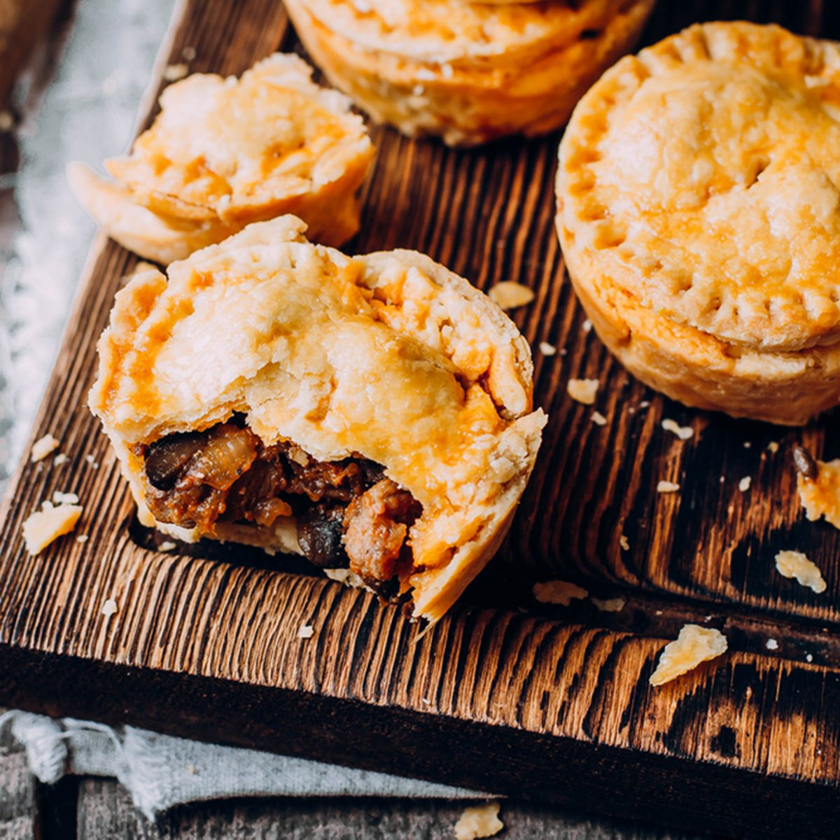 Fresh Traditional Australian meat mini pie on the wooden board on table background