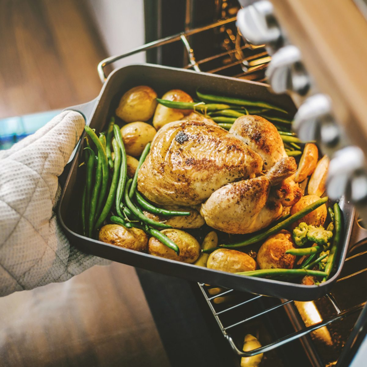 Cook taking ready fried baked chicken with vegetables from the oven. Home cooking concept. ; Shutterstock ID 1175873314; Job (TFH, TOH, RD, BNB, CWM, CM): TOH