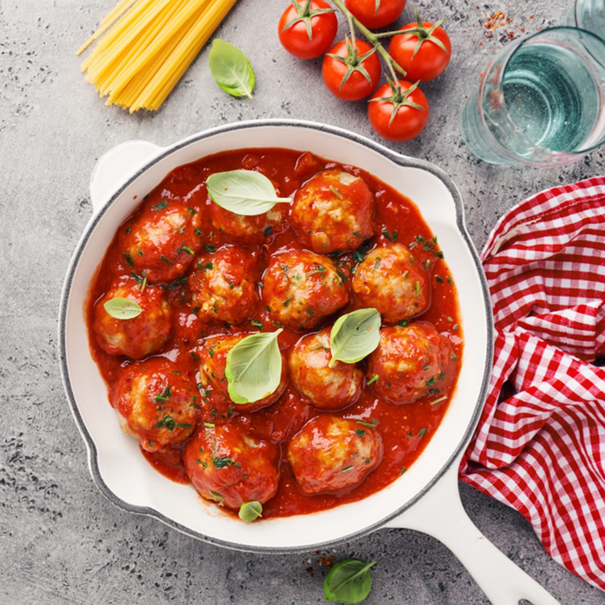 Homemade meatballs with tomato sauce and spices served in white pan on grey background. Closeup with copy space. ; Shutterstock ID 1246756819; Job (TFH, TOH, RD, BNB, CWM, CM): Taste of Home