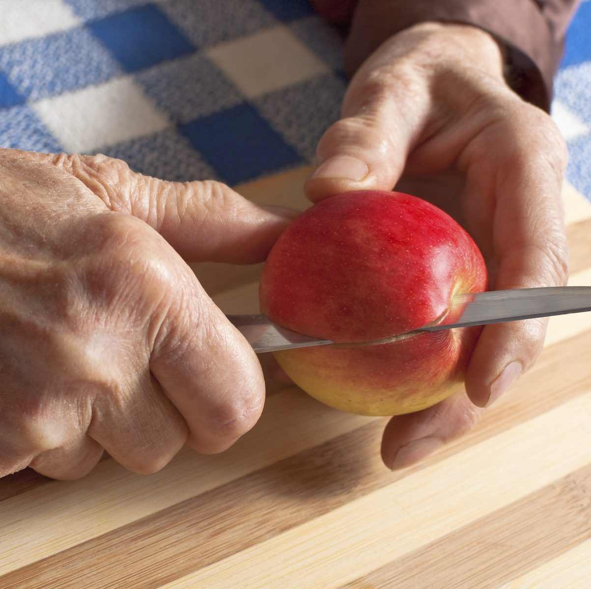 Old woman slicing an apple