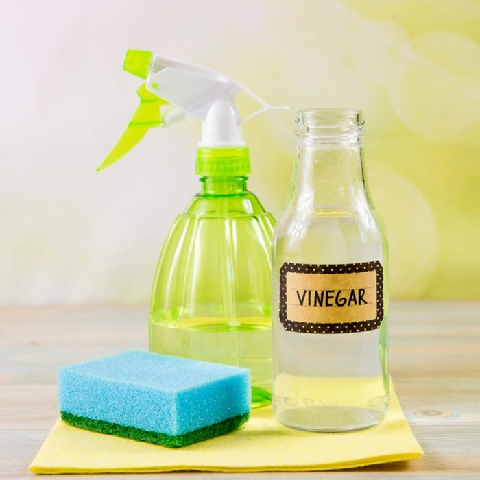 Chemical free home cleaner products concept. Using natural destilled white vinegar in spray bottle to remove stains. Tools on wooden table, green bokeh background, copy space.; Shutterstock ID 1296110344; Job (TFH, TOH, RD, BNB, CWM, CM): TOH
