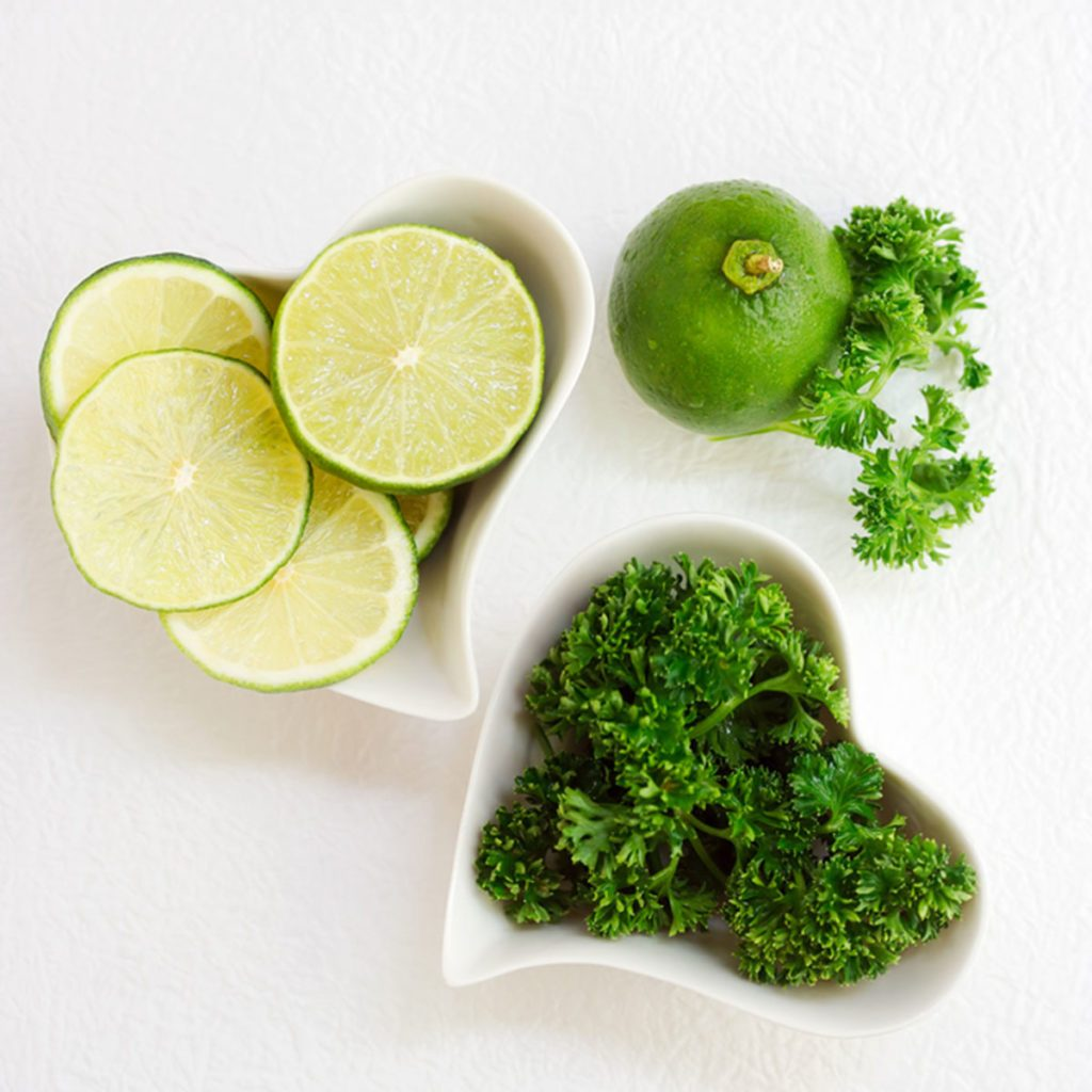 Sliced lime and celery in heart shaped plates over white paper. Green healthy drink ingredients. Fruits and vegetables background. Text space; Shutterstock ID 409140517; Job (TFH, TOH, RD, BNB, CWM, CM): Taste of Home