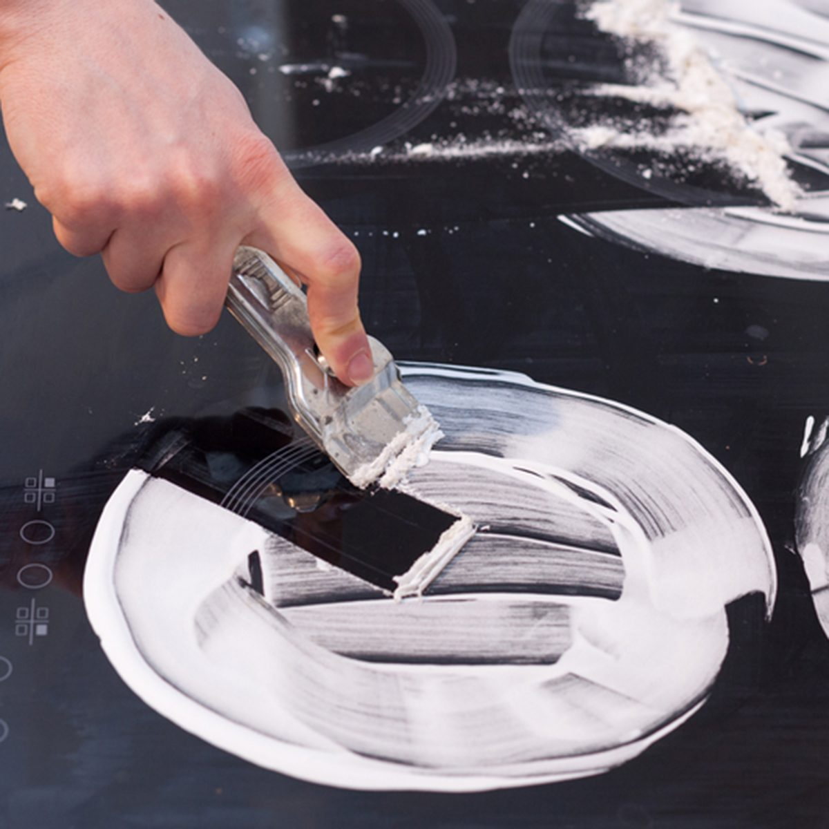 Housewife cleaning and polish electric cooker. Black shiny surface of kitchen top, hands with foam, glass scraper, bottle of cleaning agent; Shutterstock ID 675139813; Job (TFH, TOH, RD, BNB, CWM, CM): TOH