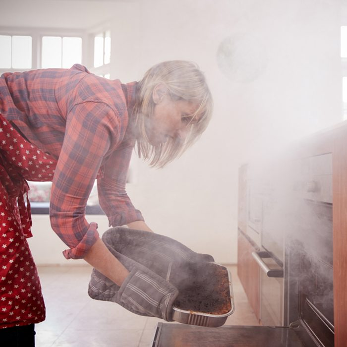 Middle aged woman opening smoke filled oven in the kitchen; Shutterstock ID 761804338; Job (TFH, TOH, RD, BNB, CWM, CM): TOH