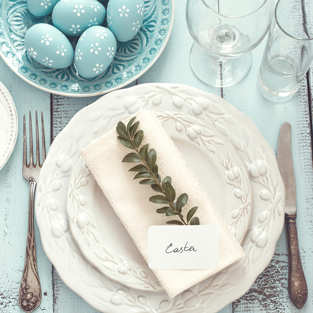 Easter table setting with holiday decor on mint wooden background