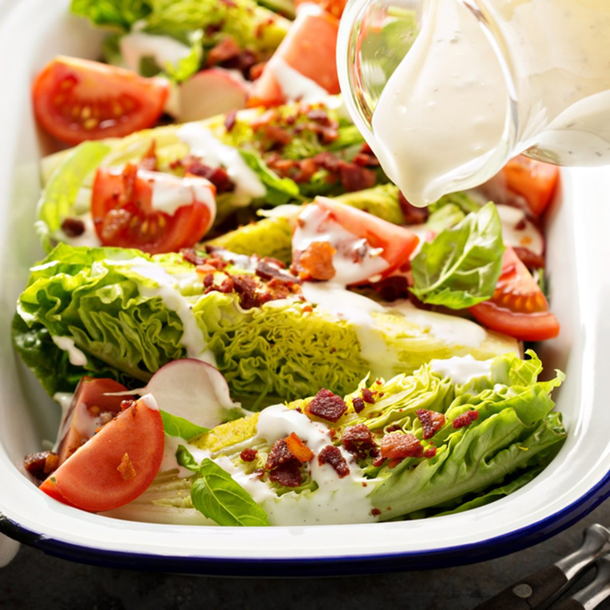 Wedge salad with baby lettuce, cherry tomatoes, bacon and ranch dressing pouring over.;