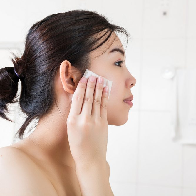 Beautiful woman removing makeup from her face in bathroom.; Shutterstock ID 557276806