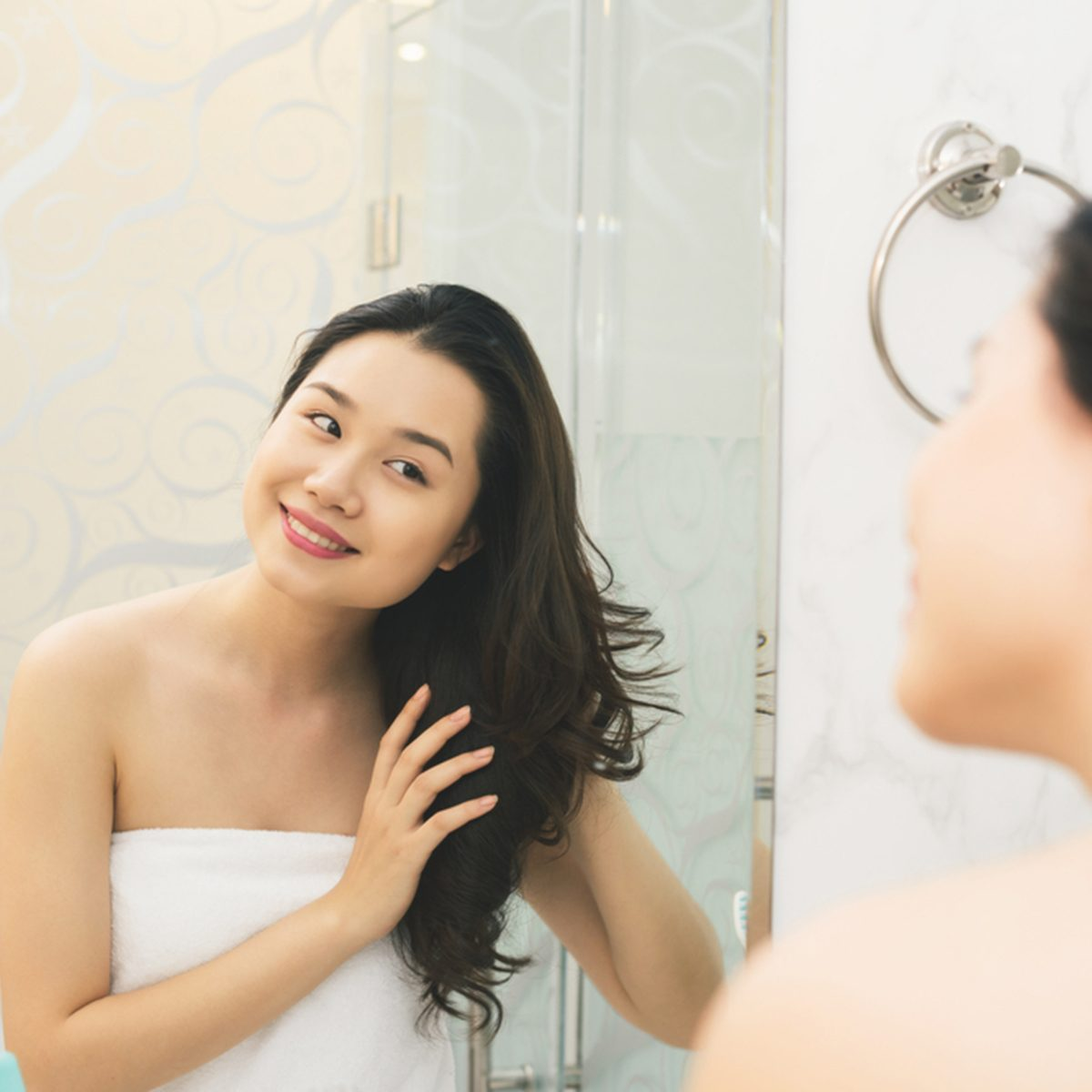 Portrait of attractive woman brushing hair in bathroom