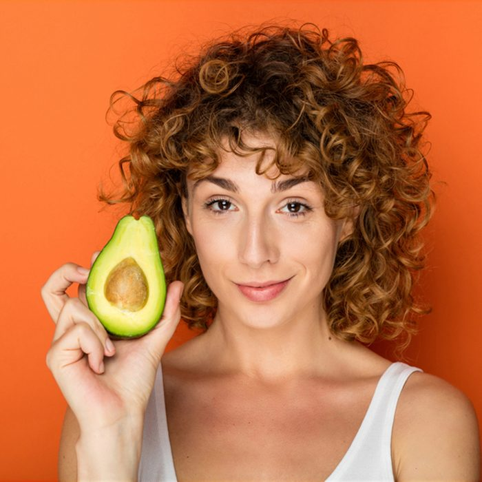 young curly woman holding a avocado in hands on orange background