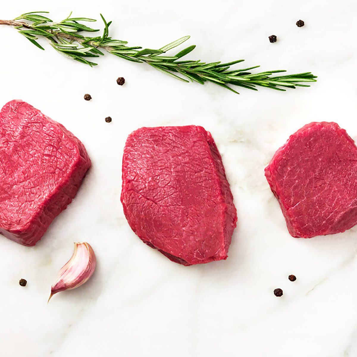 Three slices of raw meat, beef fillet, shot from above on a white marble table with a sprig of rosemary, garlic cloves, salt, and pepper