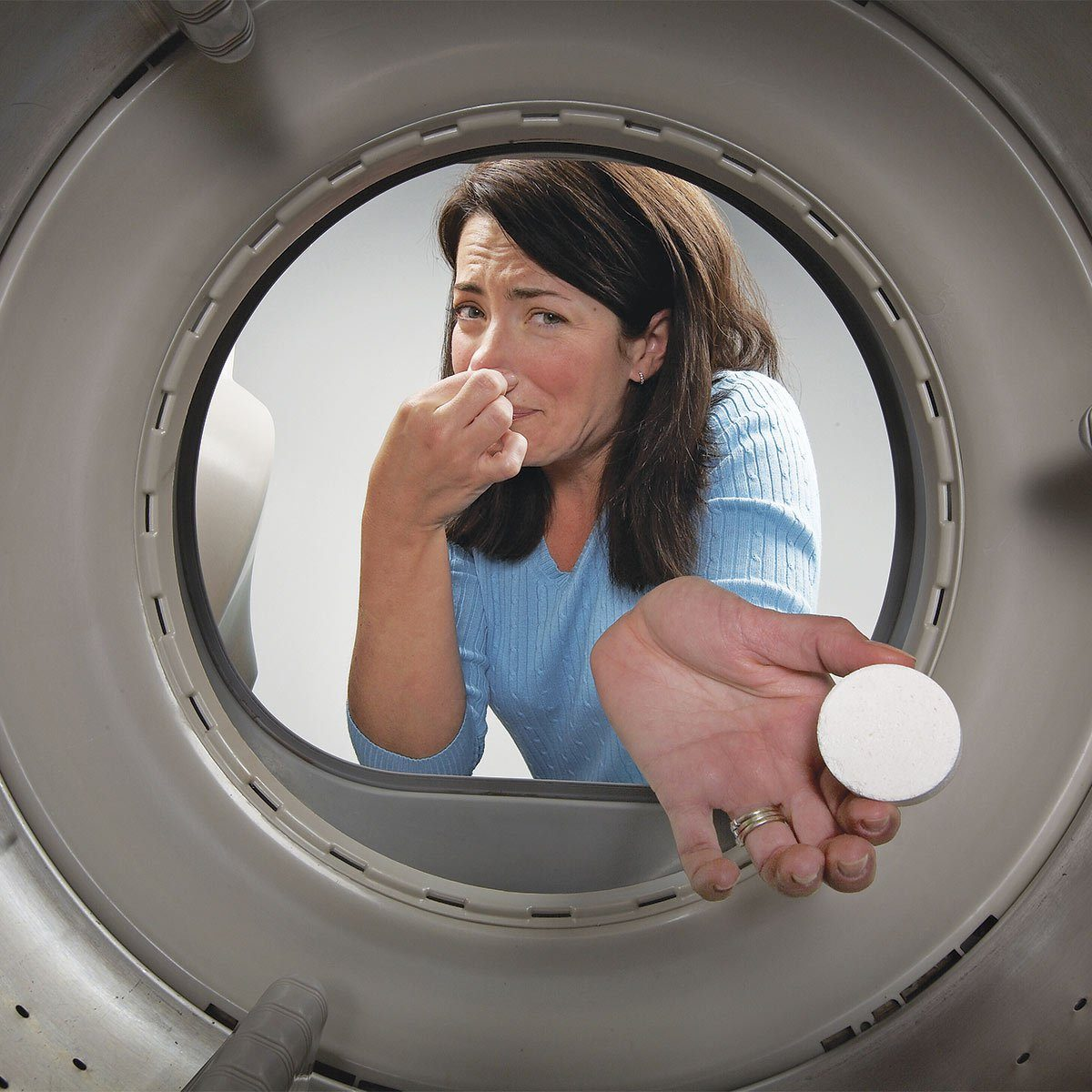 Woman pinching her nose and putting a disk into the washer
