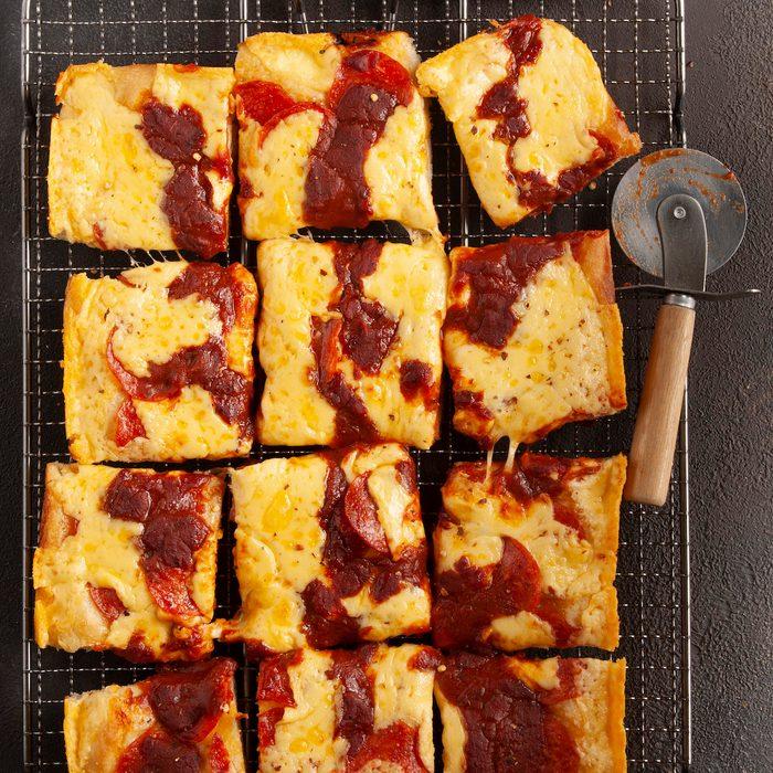A batch of Detroit-style pizza cut into squares.
