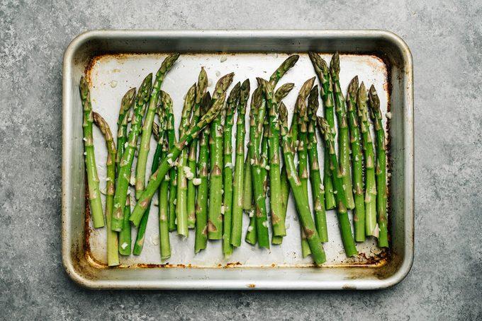 Oiled asparagus on a baking sheet ready to make roasted asparagus.